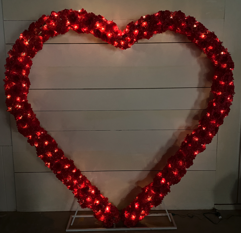 tall heart for rent with red flowers and lights wrapped around it