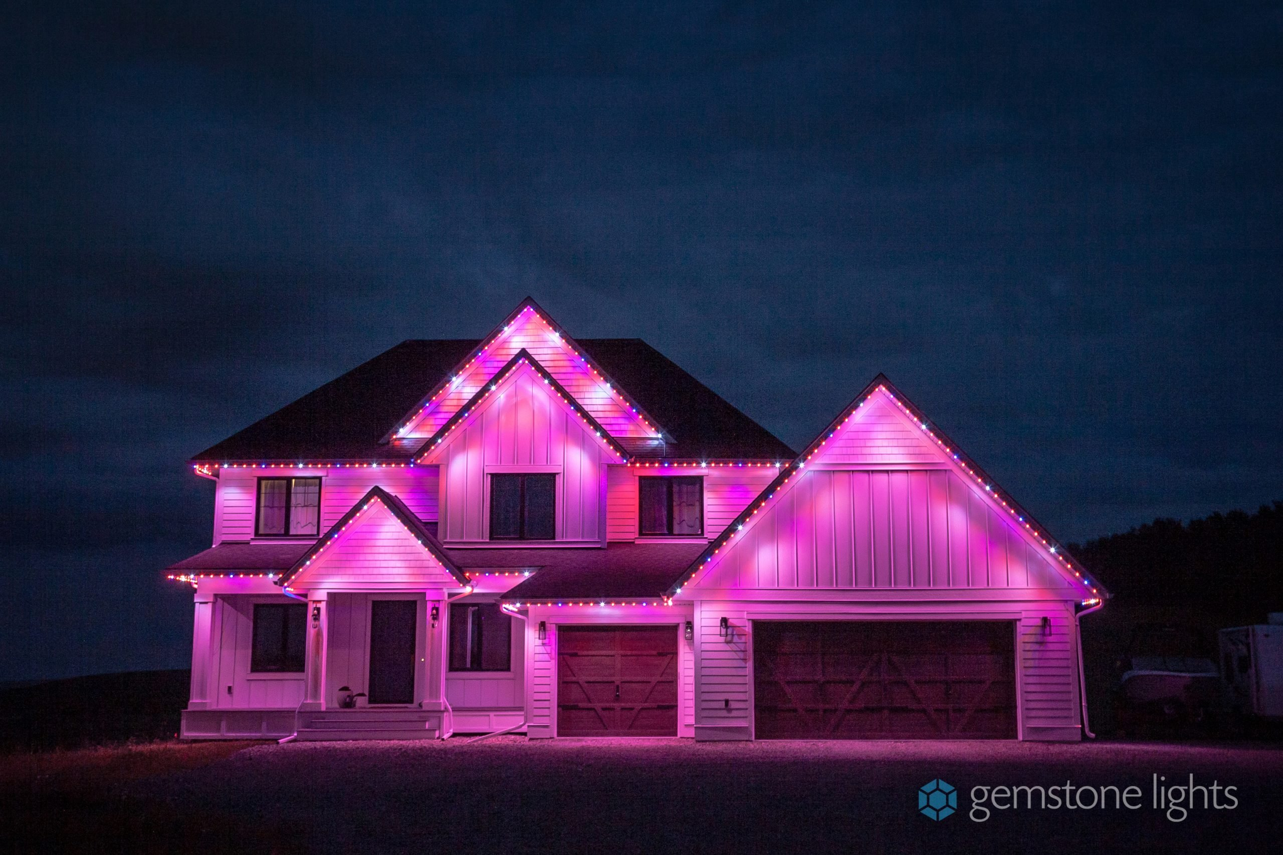 A home glowing pink from its color changing soffit lights