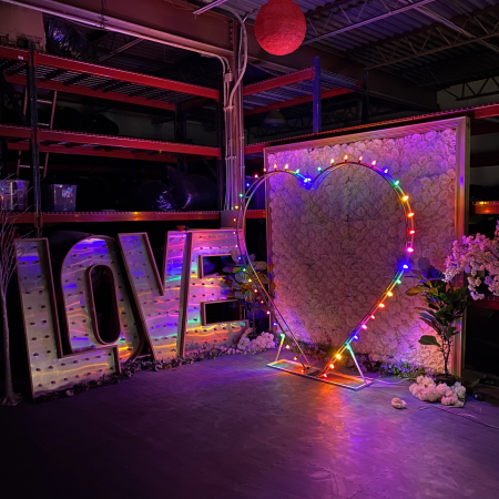 wedding decor items in the dark lit up with giant heart marquee letters and a flower wall